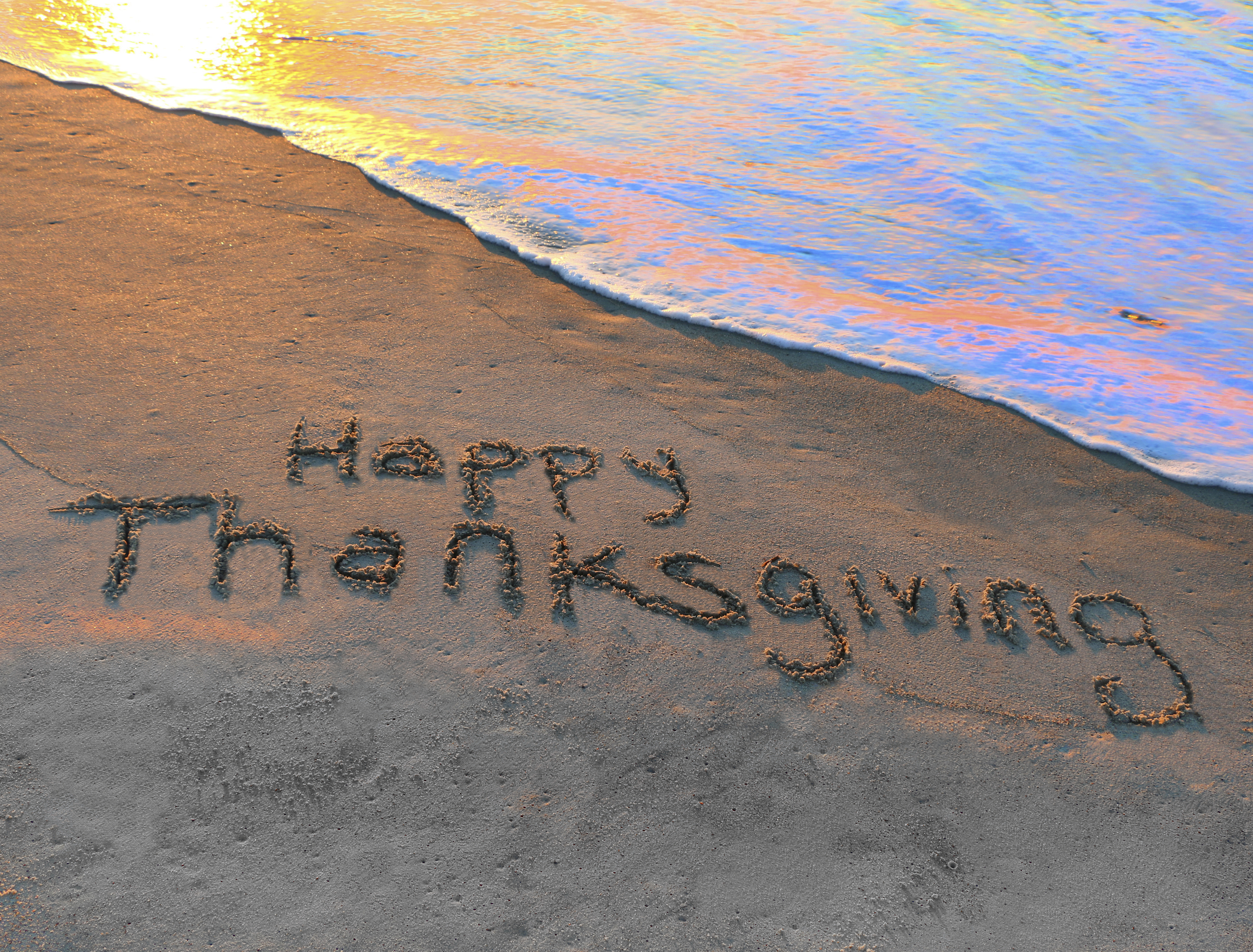 Happy Thanksgiving written in the sand on the beach
